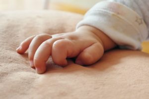 Bilingual baby hand resting on blanket.