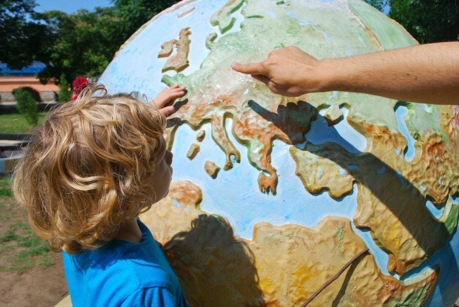 Bilingual child looking at world map