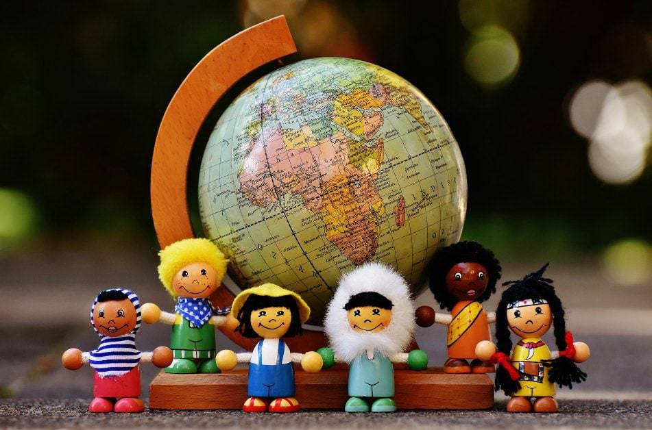 Small world dolls in front of world map