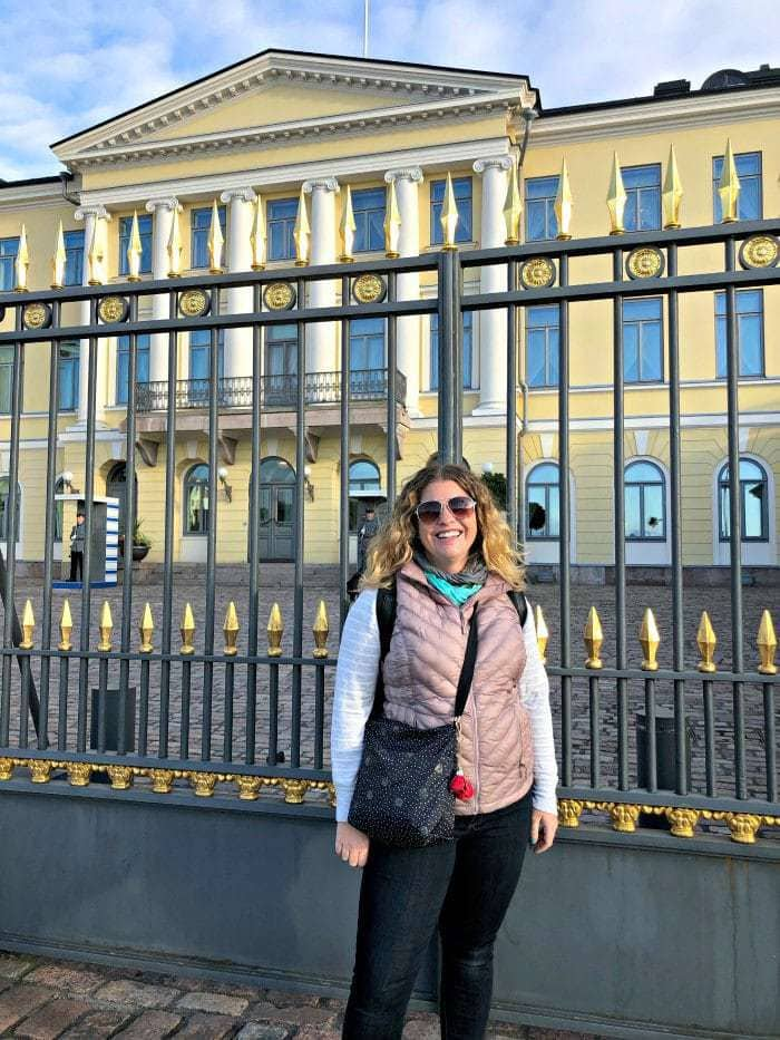 Woman standing in front of yellow parliment building in helsinki finland