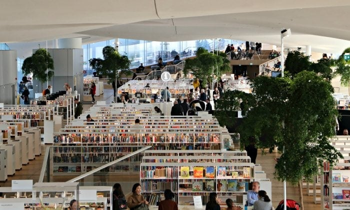 busy library with white ceiling, tall bookcases and trees growing in finland