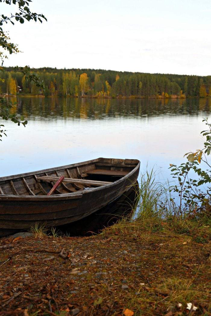 wooden boat on a lake with fall trees in finland