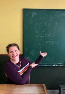 Spanish teacher in classroom in front of blackboard.
