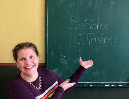 Spanish teacher in classroom in front of blackboard