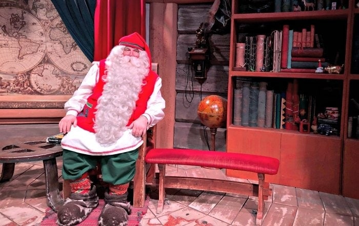 Costumed Santa Claus sitting in a rustic wooden cottage setting.