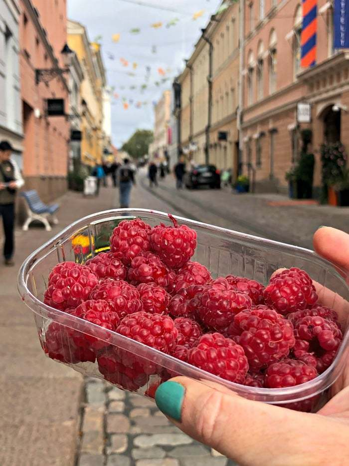 fresh raspberries in plastic container on main street in helsinki finland