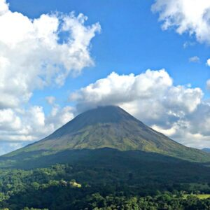 Arenal Volcano Costa Rica against a blue cloudy sky.