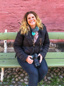 Woman sitting on a bench and holding a camera in front of a pink adobe wall.