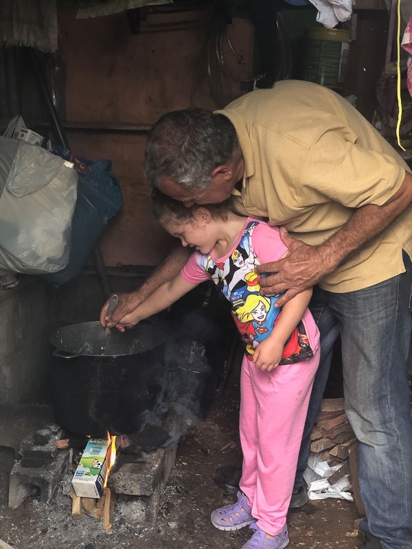 young girl stirring por of tamale masa over an open fire in costa rica with her uncle helping her