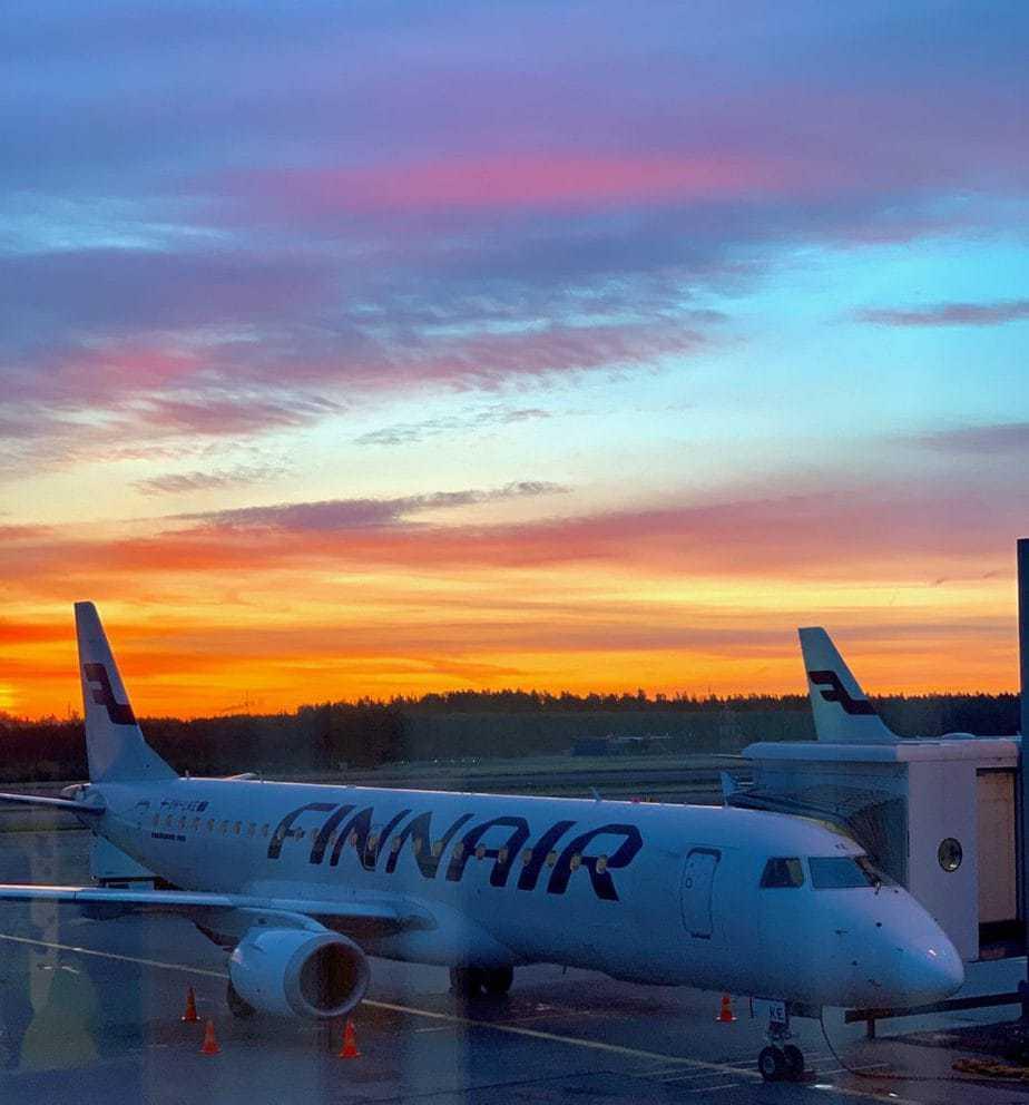 Finnair jet sitting on the tarmac at sunset.