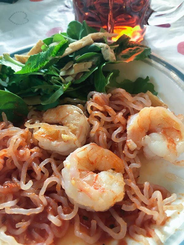 shrimp in red sauce with noodles and salad