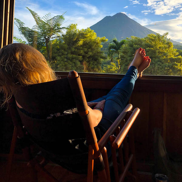 Woman in rocking chair with feet up looking at volcano in Costa Rica.