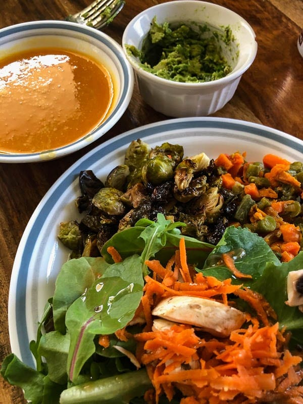 three plates of healthy food salad, bressels sprouts, soup and guacamole