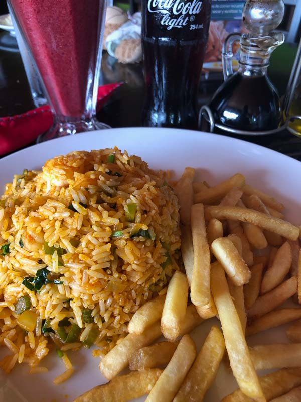 plate of arroz con pollo with french fries and diet coke at soda la parada la fortuna
