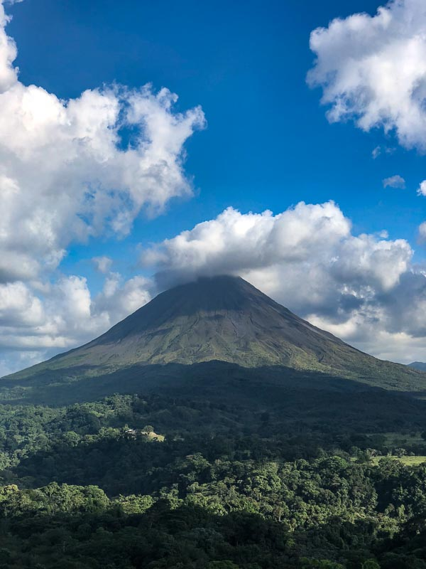 view of arenal volcano with blue sky and clouds costa rica