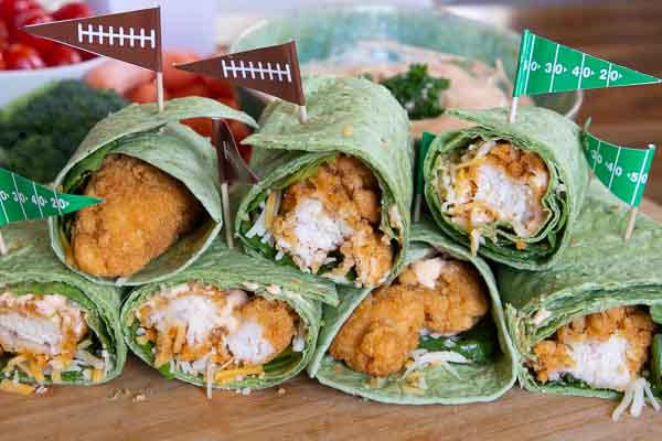 Buffalo chicken wraps with football flag toothpicks speared into them.