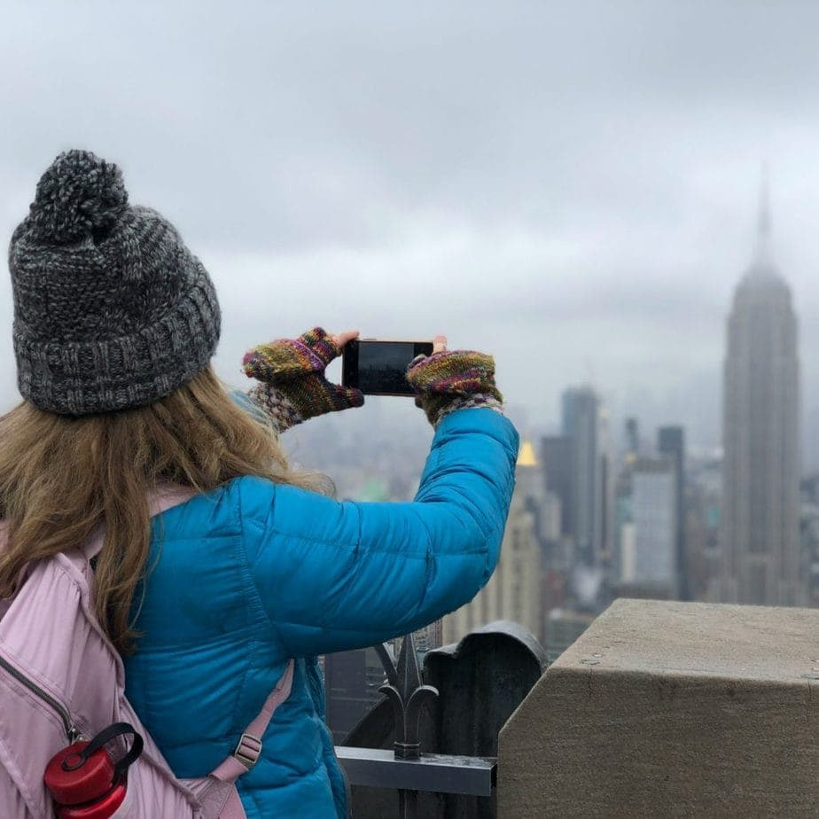 Woman taking a picture of mist shrouded city skyline.