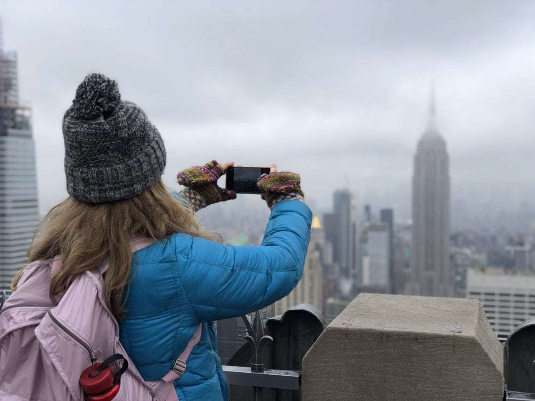 Woman taking a picture of New York City buildings from a balcony.