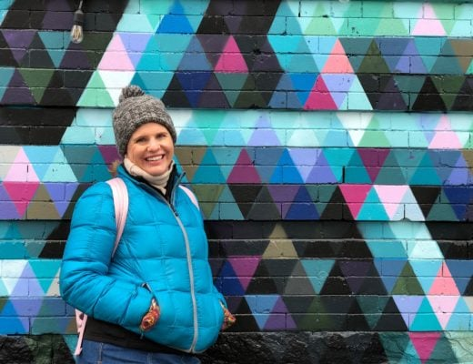 Woman wearing a winter outfit posing in front of a wall patterned with painted triangles.