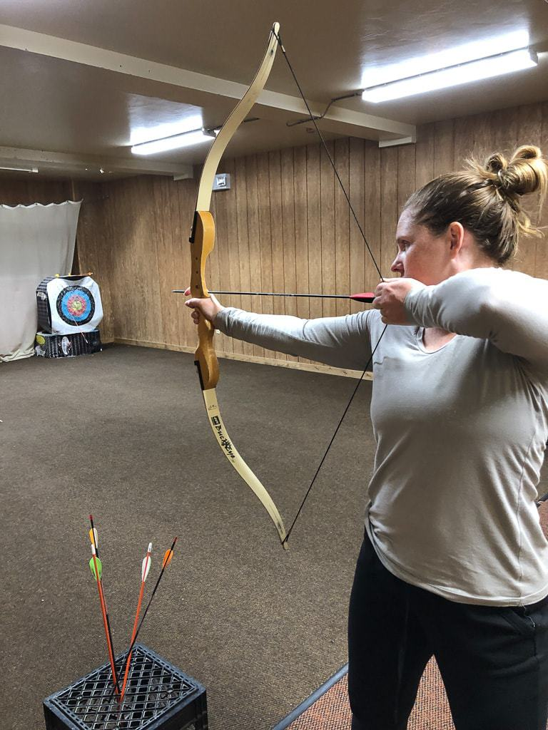 woman shooting bow and arrow in archery class