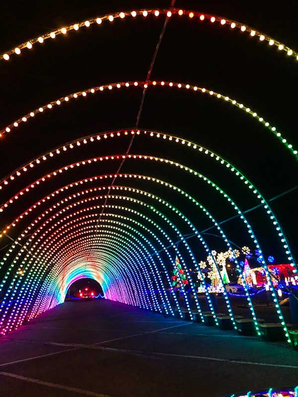 car driving through holiday light tunnel