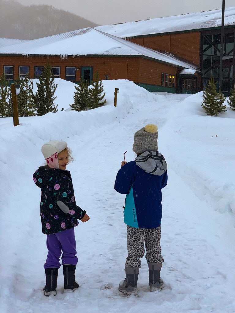 children in winter gear walking in snow outside indian peaks lodge ymca