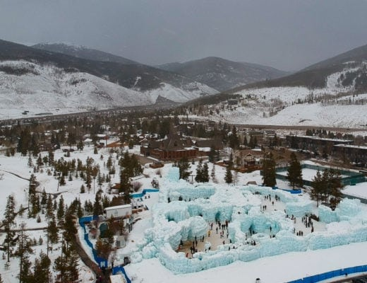 Aerial view of Colorado-based ice palace amidst pine trees and mountains.