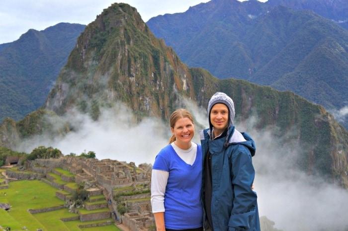Couple at Machu Picchu at sunrise in Peru.