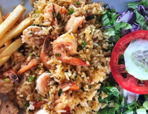 Fried rice with tail on garlic shrimp, tomato, cucumber and lettuce.