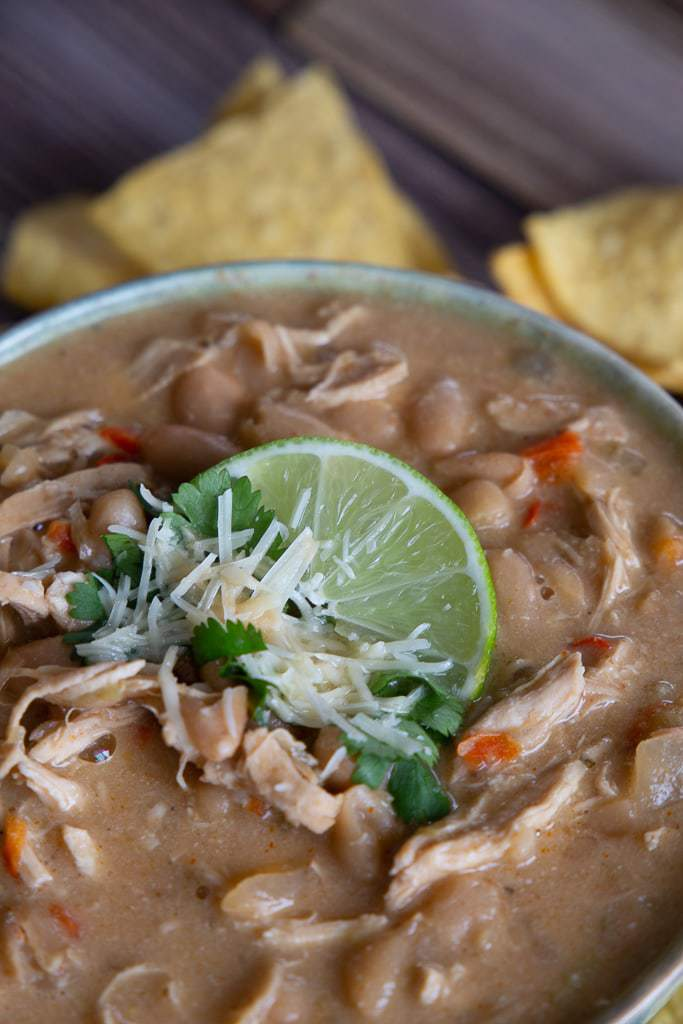 bowl of white chicken chili with cheese, lime and cilantro