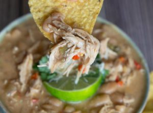 How to make a bowl of chili- chicken, sour cream, lime and great northern beans.