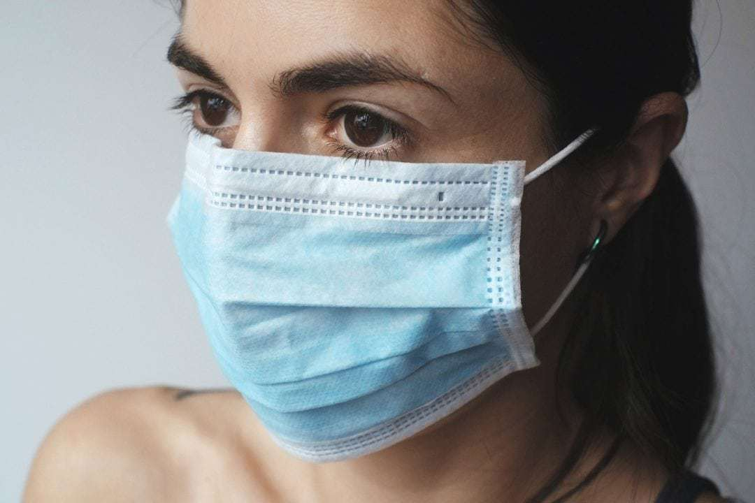 Young woman with brown eyes wearing a blue face mask.