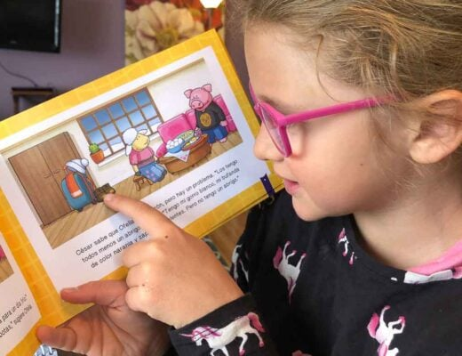 Young girl reading children's book with Spanish text.