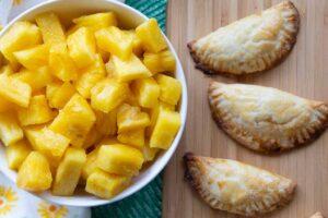 costa rican pineapple empanadas with large bowl of fresh pineapple