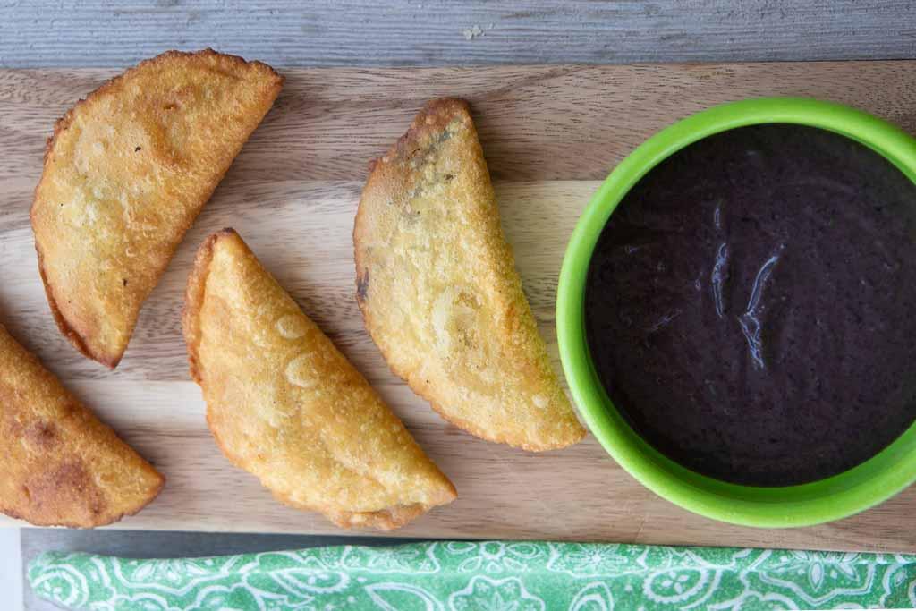 Four bean empanadas and green bowl of black bean puree.