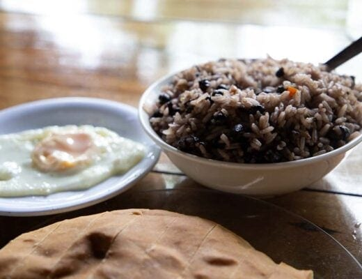 Beans and rice, fried egg, and pan casero together on a wooden tabletop.