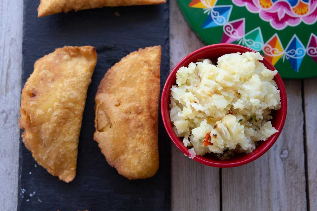 Vegan potato empanadas and small red rampkin of filling.
