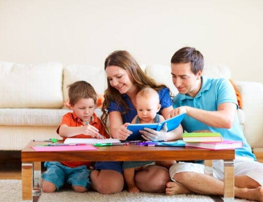 Young and smiling family with two children reading and drawing at their coffee table.