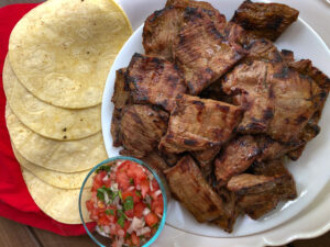 White plate of carne asada with salsa and tortillas.