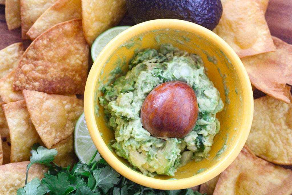 Yellow bowl of guacamole surrounded by tortilla chips.
