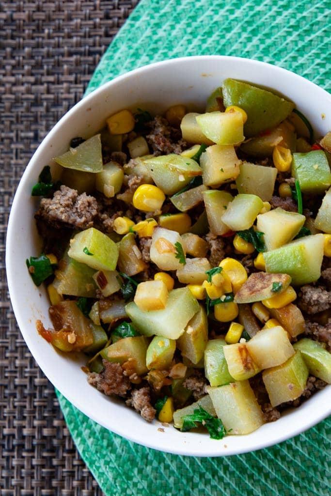 white bowl with picadillo and cilantro garnish