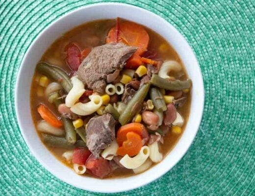 Bowl of vegetable beef soup on a light blue mat.