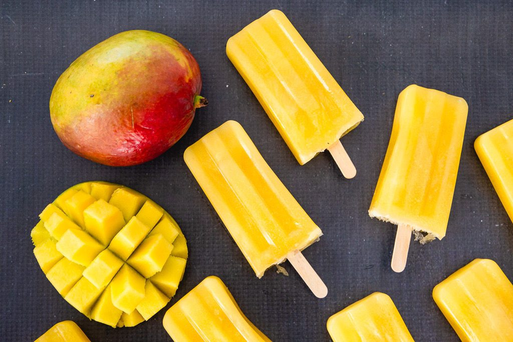 Multiple mango popsicles pictured beside a sliced mango and a whole mango.