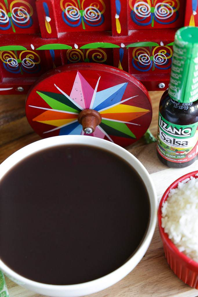 black bean soup with salsa lizano and red costa rican ox cart in background