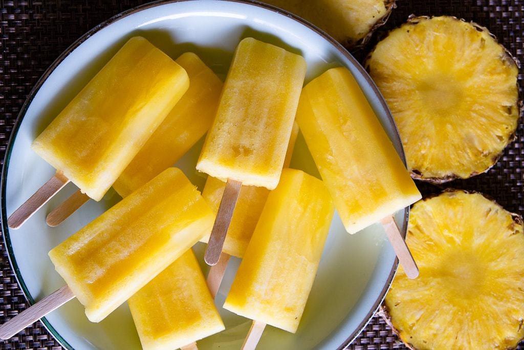 Series of pineapple popsicles arranged on a plate beside rings of fresh pineapple fruit.