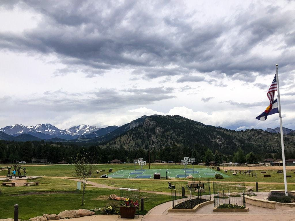 YMCA of the Rockies main field featuring basketball courts, picnic areas, benches, and a statue.