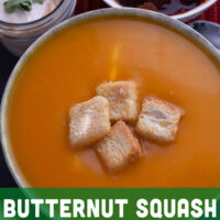 A bowl of the butternut squash soup with croutons in the center.
