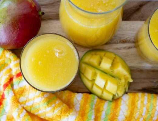 Aerial view of several glasses of mango juice and mango fruits.