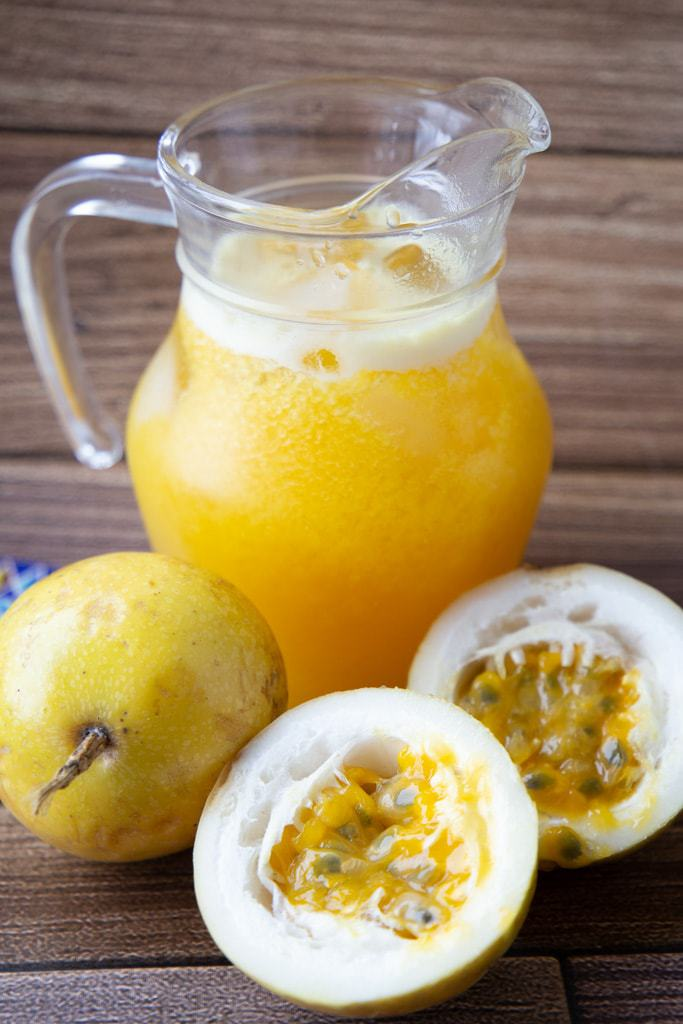 Pitcher of passion fruit juice beside halved yellow passion fruits.