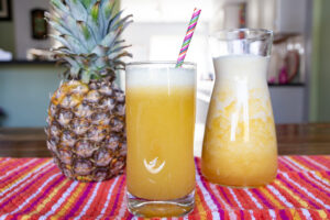 Pineapple fruit, glass of pineapple juice, and carafe placed on a striped cloth.